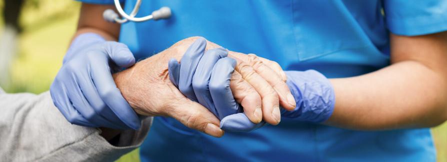 Caregiver holding patient hand